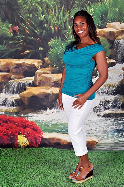 Sakinah Bellamy posing by waterfall in article about holistic healing.