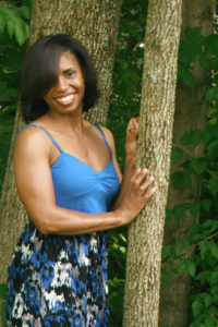 Naturel Max Health LLC: Sakinah Bellamy, Owner and Holistic Health Coach posing by tree.